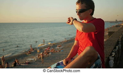 Young handsome man in sunglasses relaxing near the sea beach with smart watch. He checks messages on social networks at sunset on smartwatch.