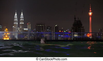 Woman relaxing in rooftop swimming pool at night, Kuala...