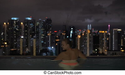 Couple looking at night Kuala Lumpur from rooftop pool,...