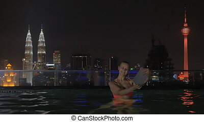 View of woman in swimming pool on the skyscraper roof making selfie by tablet against night city landscape. Kuala Lumpur, Malaysia