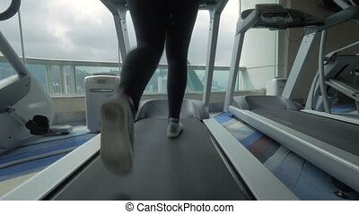Woman training on treadmill and enjoying cityscape - Young...