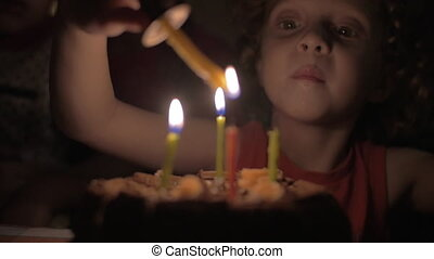 Slow motion view of small girl lighting the candles on birthday cake in the dark