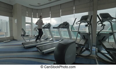 Woman working out on running machine and looking at city -...