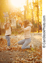 Mother and daughter throw up fallen leaves. - Family walk....