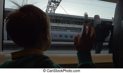 Child in train waving hand to grandparents as he leaving -...