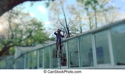 worker girl washing glass house with high pressure. - worker...