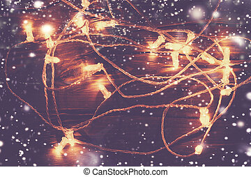 Christmas lights on dark background close up with snowflakes