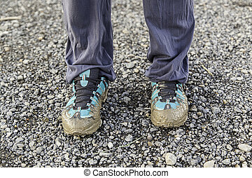 Muddy shoes, detail of a dirty and bedraggled pilgrim