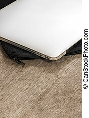 Laptop put on black soft case on wooden table