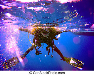 Scuba diver - A scuba diver floating on the surface without...
