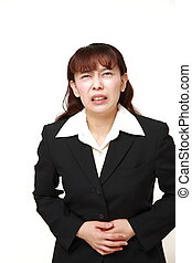 Asian businesswoman suffers from stomachache - concept shot...