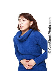 Asian woman suffers from stomachache - concept shot of Asian...