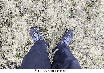 Muddy shoes, detail of feet of clay