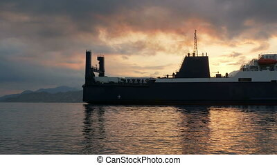 Large ship sailing into the port at sunrise over the ocean. Mountains and orange sun against the background of the ship. cargo carriage concept