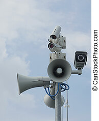 Security cameras and loudspeakers against of blue cloudy sky
