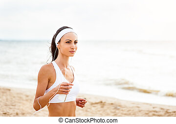 Woman runner running on the beach listening to music on smartphone using earphones.