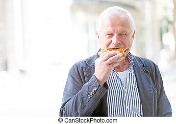 Senior man eats a pizza