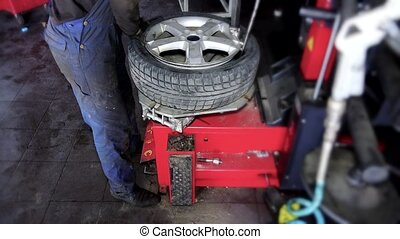 auto mechanic using special equipment to change tires in garage.