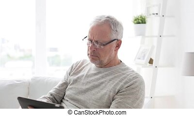 senior man with tablet pc at home - technology, people and...