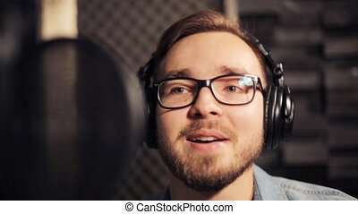 man with headphones singing at recording studio - music,...