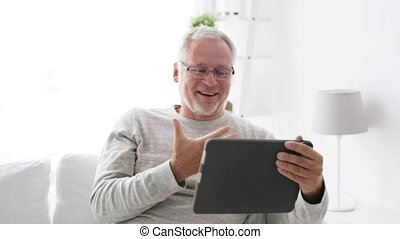 senior man having video call on tablet pc at home 119 -...