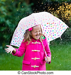 Little girl with umbrella in the rain - Little girl playing...