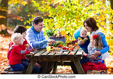 Family having picnic in autumn - Happy young family with...