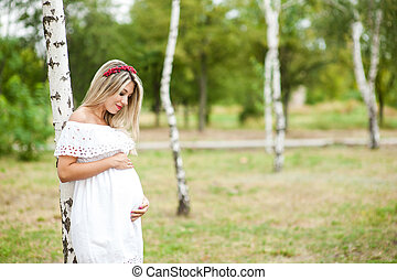 Beautiful lovely girl wearing her first child in the stomach and is looking forward to his birth.