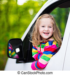 Little girl sitting in white car - Little girl with funny...