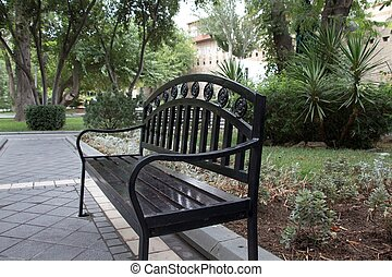 Black bench in a park with the trees background