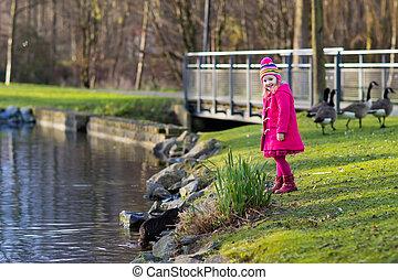Kids feeding otter in autumn park - Little girl feeding...