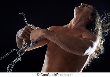 Young man with long hair breaks the iron chain. Strong....