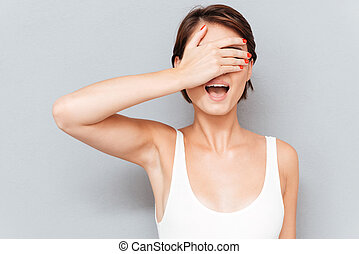Portrait of a young woman covering her eyes with palm...