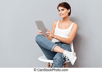 Smiling young woman holding tablet pc computer isolated