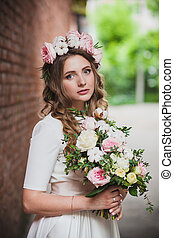 bride in a wreath of flowers with her hair, summer wedding,...