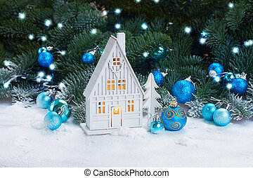 White christmas house glowing with decorations and lights in...