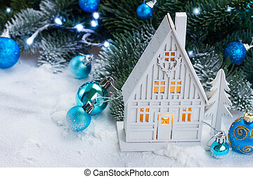 White christmas house glowing with blue decorations and...