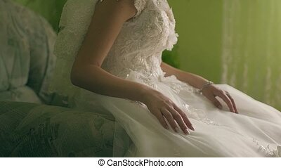 The beautiful bride in a white dress sits on a brown background