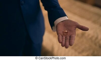 Wedding rings on the palm of the groom, marriage proposal...