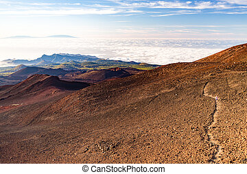 Inspirational landscape with woman running on mountain trail
