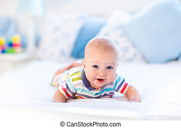 Baby boy in bed - Adorable baby boy in white sunny bedroom....