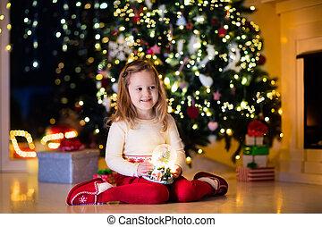 Little girl holding snow globe under Christmas tree - Family...
