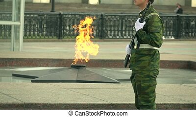 Memorial fire and armed guard in camouflage uniform. Super...