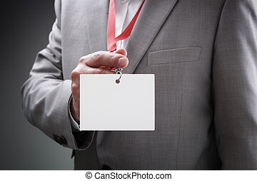 Businessman holding blank ID badge - Businessman at an...