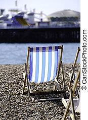 deckchair - a single empty deckchair on a pebbly beack...