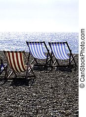 Deckchairs - a group of empty deckchairs on a pebbly beach...