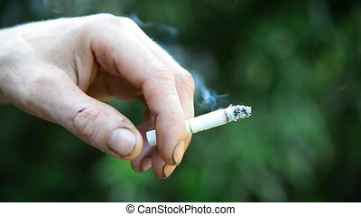Man hand with a cigarette on background of nature