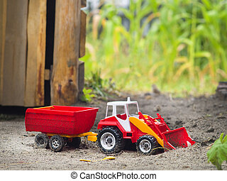 Toy tractor - Children plastic machine in the sandbox. Toy...