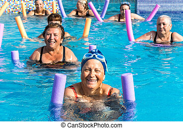 Group of senior women at aqua gym session. - Group of active...