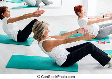 Middle aged women doing abdominal exercise in gym.